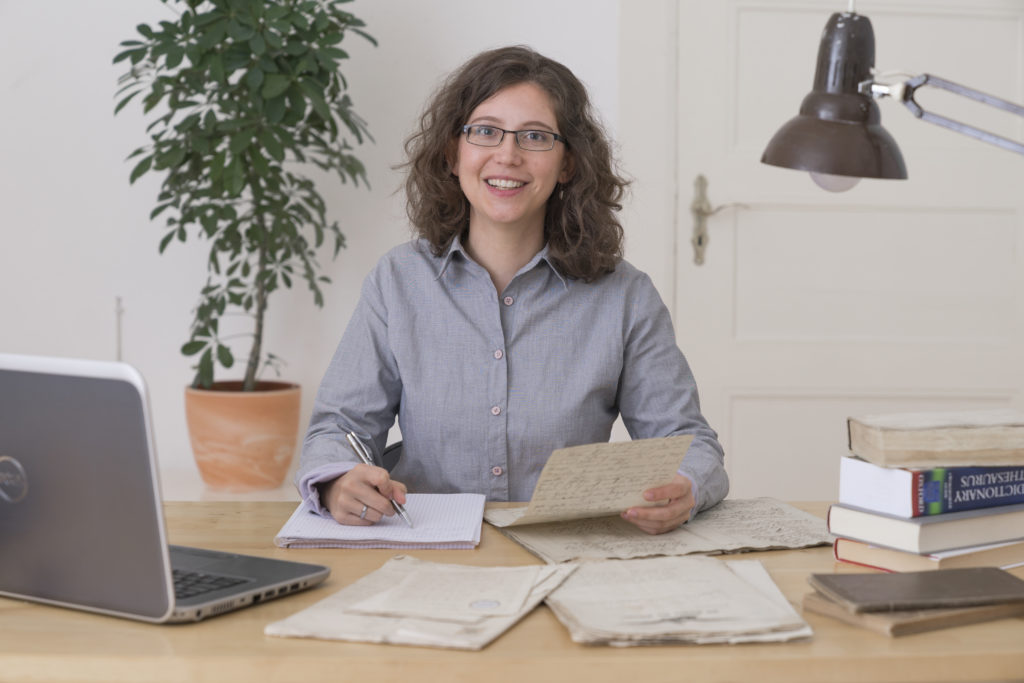 A young woman is sitting at a wooden desk and working on a translation. She has several documents in old German script are lying in front of her. There are also some books and a laptop on the table.