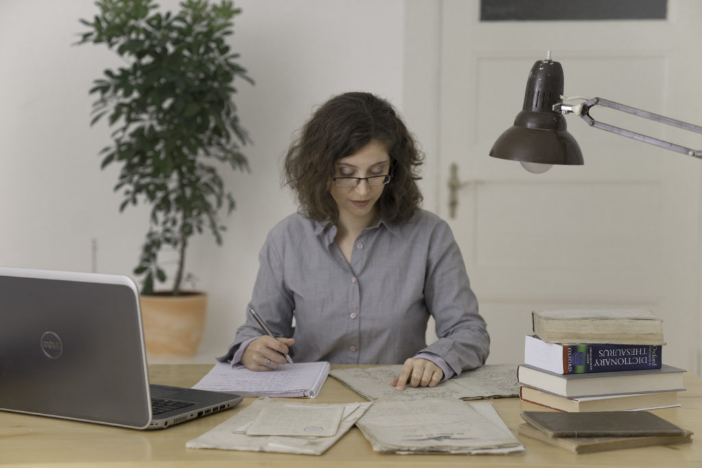 A young woman is sitting at a wooden desk, working on a translation of an old document.