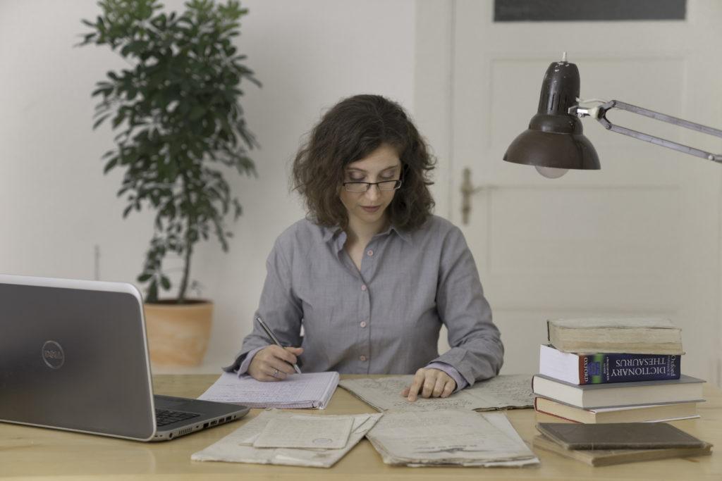 Eine junge Frau sitzt an einem Schreibtisch, auf dem sich verschiedene Unterlagen, Bücher und ein Laptop befinden. Ihr Blick ist auf ein altes Dokument gerichtet.