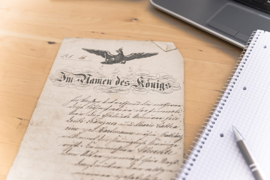 "An old document in Kurrent script is lying on a wooden desk, next to a noteblock and a laptop. The document's title reads ""Im Namen des Königs""."